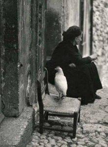 abuela con gallina a la puerta de casa